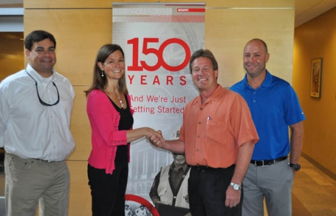 Castle Contracting founder Julie Ledbetter shakes hands with McCarthy Building Companies, Inc. Central Division president Scott Wittkop. Also pictured (on left) is current Castle president Rich Ledbetter and (on right) current Castle chief operating officer Mike Myers.